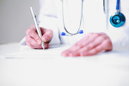 Photography closeup of a female doctor writing a prescription