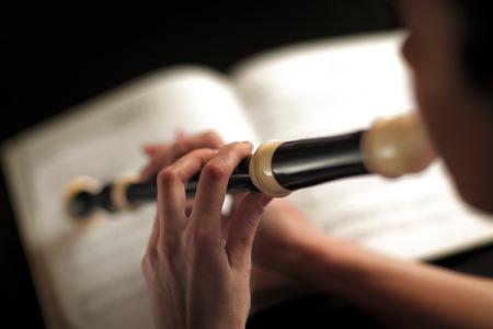 flauta dulce: detalle fotografía de una mujer que toca la flauta foco en los dedos Foto de archivo