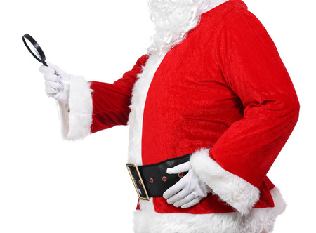 photography of Santa Claus holding a magnifying glass