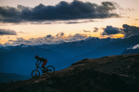 yourself: A mountain biker riding down a mountain at sunset.