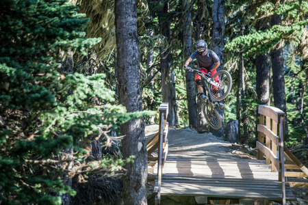 yourself: A mountain biker catching a big air on a trail.