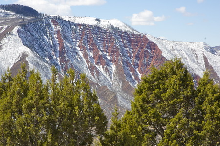 snow on red rock hillside,