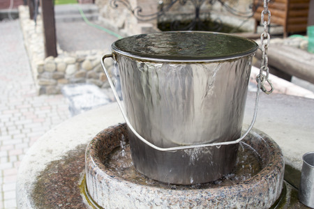 worthless: water is coming out of a metal bucket Stock Photo