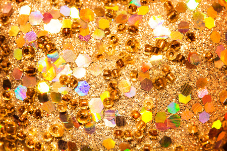 sequins: Gold glitter texture with rings and various geometric figures. Background abstract.