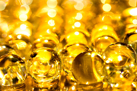 Gold shiny water gel balls. Macro photo, can be used both for advertising or cosmetics, jewellery and for medicine. Abstract background. Stock Photo