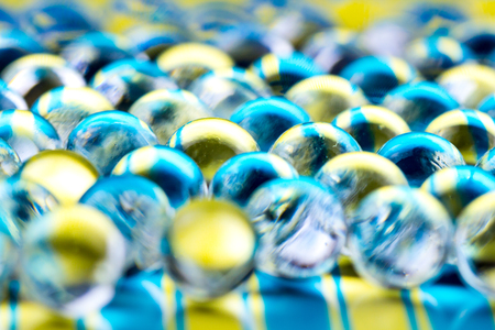 Blue and yellow water gel balls. Macro photo, can be used both for advertising or cosmetics and for medicine. Abstract background.