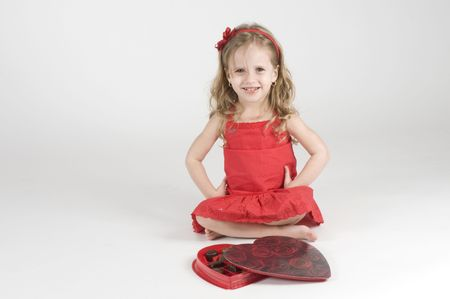 Little Girl sitting infront of a heart shape chocolate box photo