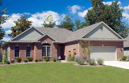 Beautiful brick ranch home against a blue cloudy sky. Stock Photo