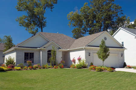 Well landscaped brick ranch with a vibrant blue sky background. Very colorful photo.