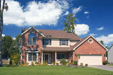Beautiful brick home with a gorgeous blue cloudy sky. This is one of many in my home series. Stock Photo