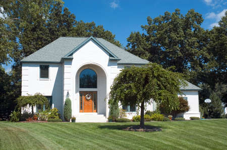 Beautiful white brick home featuring an arched entryway with a huge arched window. Simple clean design. Just one in a series of homes in my collection. Stock Photo - 251536
