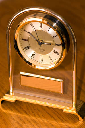 A brass clock with space in the front for text. photo