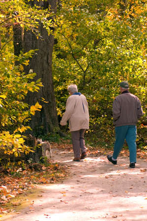 An older couple enjoying a walk in the park on a nice autumn day.