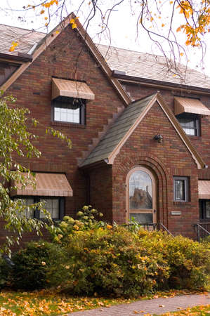 awnings: A beautiful arched brick entryway highlights this home.