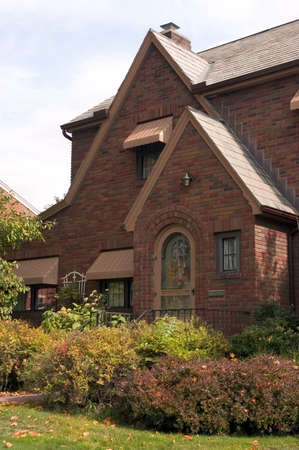 awnings: Classic design in this brick home with its arched entryway. Beautiful detailed brickwork and beautifully landscaped lawn.