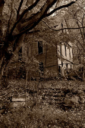 A vertical photo of an old abandoned house that would make a great haunted house image for Halloween.