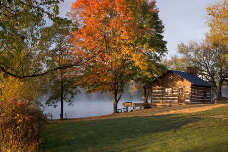 A log cabin on the edge of a lake with early morning mist riseing form the lake and fall tree colors.