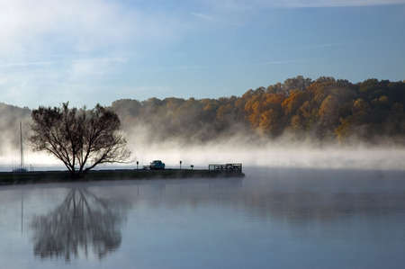 Foggy morning at the lake. A man sits in his truck watching the scene unfold before he begins to fish.