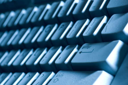 A macro of a keyboard with a blue tone and shadows from off camera  lighting. Lots of detail, you can see the raised letters in the  Shift key. Shallow depth of field with focus on the Enter key area.