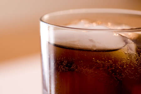 the carbonation: A close-up of a glass of cola on ice.