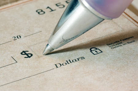 Close-up of a person filling out a dollar amount on a check, focus is sharp and on the pen tip and the dollar word and symbol.
