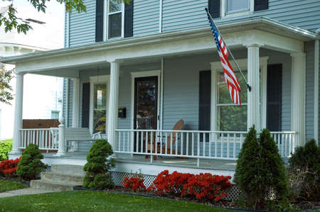 A typical front porch of a home in a small town in  the U.S.A. Featuring an American flag proudly flying and a porch swing to enjoy the spring day. photo