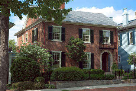 House with federal style architecture . This red brick home is a good example of the formal style. Features some wrought iron detailing with the balcony and fence.