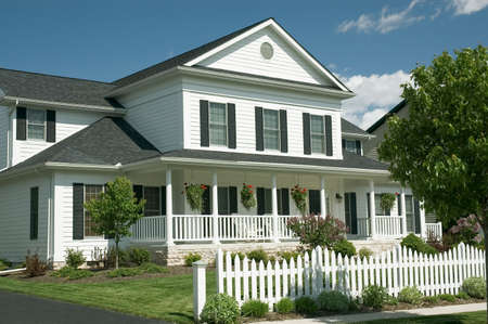 New home with an old country feel. Large front porch and the white picket fence for the old time retro look. Just one of many new house photos in my gallery. Stock Photo