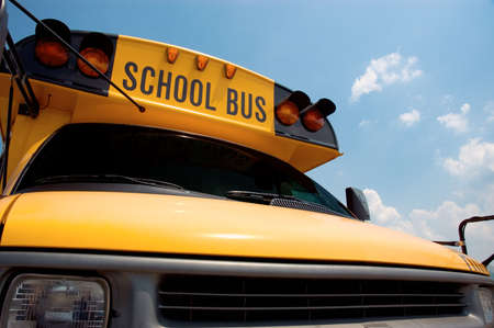 precaution: Close-up of the front of a school bus with a blue sky background.