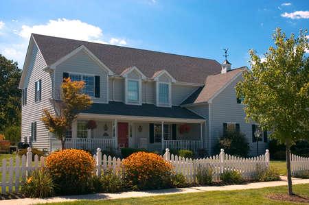 Mooi allemaal hout nieuw thuis met traditionele Amerikaanse country-stijl-architectuur. Grote veranda met stoelen en een schommelstoel veranda schommel. Afgeboekt mooi met een wit hek paal en mooie cottage tuin bloemen. Stockfoto - 506967