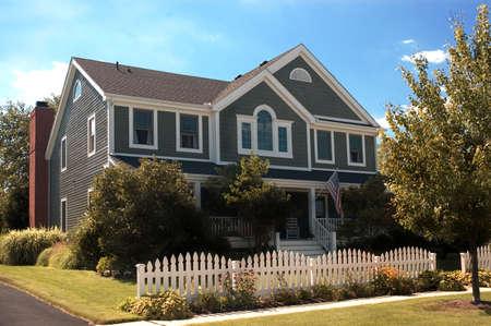 front porch: Hermosa casa de madera de color gris con una bandera americana y un pa�s grande estilo porche delantero.