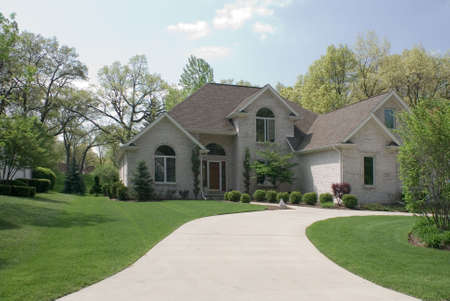 Beautiful beige brick home featuring a complex roof design, circular driveway and formal landscaping. Stock Photo
