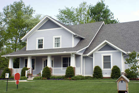 Beautiful new country style wood home featuring a large front porch and nice landscaping. Stock Photo