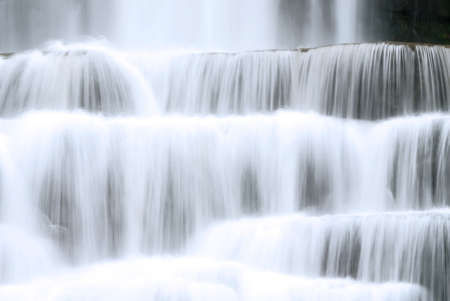 Colse up of a waterfall as the water is tumbling over its rock ledges. Taken with a slow shutter speed to soften and smooth out the water. Banco de Imagens - 1052379