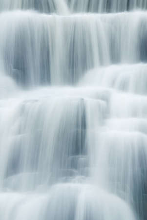 A close-up of a waterfall showing the smooth veil lines of the flowing and tumbling water. Given a slight blue tint for a fresh ,clean, pure look.