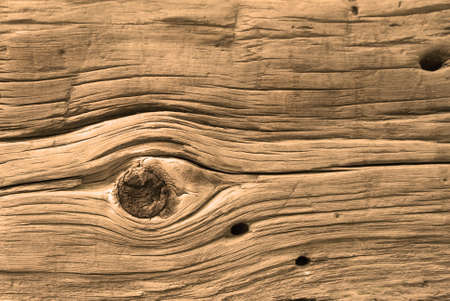Aclose-up of an old antique log from a log cabin. Features a large knot that resembles an eye. Lots of nice texture and would make a nice background.  Stock Photo