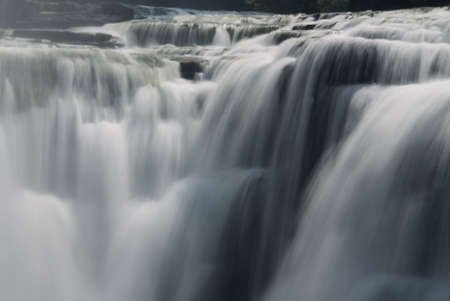 A close-up of a powerful waterfall showing the smooth veil lines of the flowing and tumbling water. Given a slight blue tint for a fresh ,clean, pure look. Lts of interesting details in the photo at full size.
