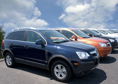 New fuel efficient SUVs on a car dealers lot for sale.  Editorial