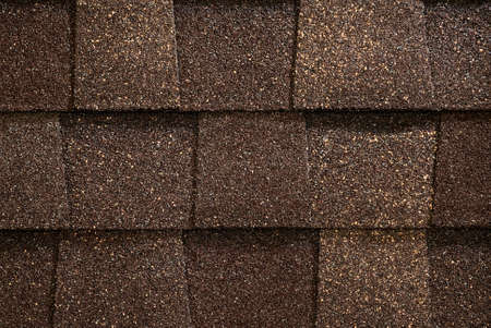 A close-up of brown toned architectural style asphlat roofing shingles.