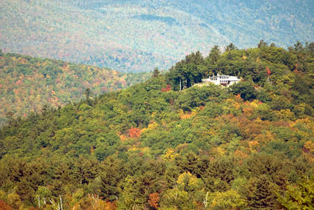 A home high up on the mountain surrounded by the colorful trees of autumn. Mount Washington is directly behind the house in the background.