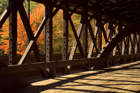 Interior details of a wooden covered bridge with the beautiful colors of the autumn trees as a background.  Stock Photo