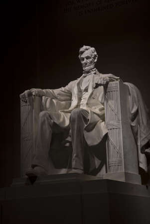 A night time shot of Abraham Lincolns statue inside the Lincoln Memorial. Located on the National Mall in Washington DC.