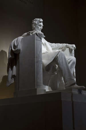 A night time shot of Abraham Lincolns statue inside the Lincoln Memorial. Located on the National Mall in Washington DC. photo