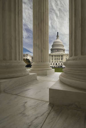 The United States Capitol Building in Washington DC, framed with the Supreme Court columns.