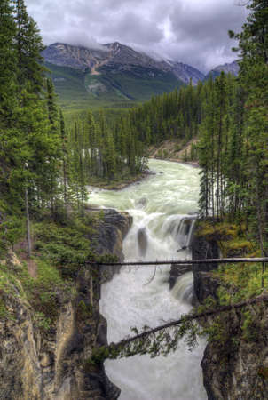cascade: Sunwapta Falls in Jasper National Park, Alberta Canada. Seen along the Icefield Parkway. The waterfall is about 60 feet tall. This is actaully the upper falls and is the one most people see. The lower falls is a short hike away and is also very iimpressiv Stock Photo