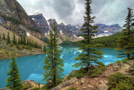 The incredible turquoise  blue water of Moraine Lake in Banff National Park in Alberta Canada. The amazing color is natural and is caused by light reflecting on the rock flower which is suspended in the water. The glaciers grind up the rock as they move photo