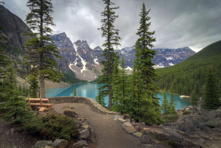 banff: The incredible turquoise  blue water of Moraine Lake in Banff National Park in Alberta Canada. The amazing color is natural and is caused by light reflecting on the rock flower which is suspended in the water. The glaciers grind up the rock as they move Stock Photo