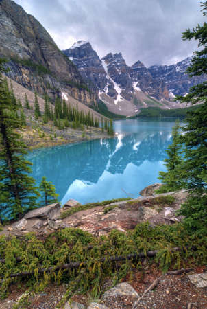The incredible turquoise  blue water of Moraine Lake in Banff National Park in Alberta Canada. The amazing color is natural and is caused by light reflecting on the rock flower which is suspended in the water. The glaciers grind up the rock as they move Stock Photo