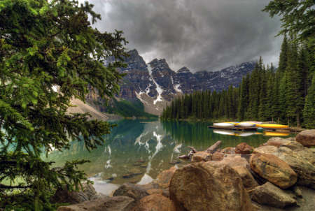 The incredible turquoise  blue water of Moraine Lake in Banff National Park in Alberta Canada. Canoe rentals make for a memorable trip to the lake. The amazing color is natural and is caused by light reflecting on the rock flower which is suspended in t