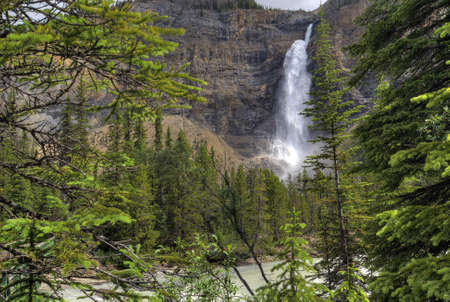 thundering: The thundering waters of Takakkaw Falls in Yoho National Park in British Columbia Canada. This popular tourist attraction features the torqouise blue waters of glacier melt. It tumbles down 830 feet into the Yoho river below.